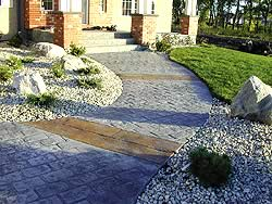 Curved stamped concrete walk way to a house. The walk way has two patterns of stamped concrete, one brick which matches the houses columns the other larger brick paver style in a lighter color.
