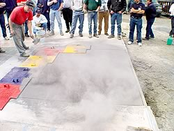 A concrete slab has been covered in a color release agent prior to a concrete stamp being placed upon the perfectly cured concrete slab.
