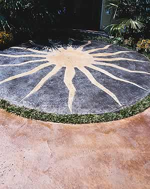Acid stained concrete application is used to create this outdoor space where the artist stained a sun on the patio to add an artistic touch to the outdoors.
