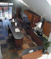 An overhead view of a large kitchen with a concrete countertop on the cooking island.