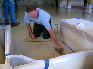 Contractor uses a trowel on a white concrete floor to create the look he is after