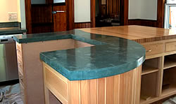 Precast concrete countertop on a teal blue color contrasts against the wood cabinets.