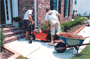Two men and a wheel barrow filling a concrete curbing machine with integrally color concrete in a tight space.