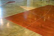Acid stain with graphic tape on a polished concrete floor. The graphic tape is used to give movement to a symmetrical floor.