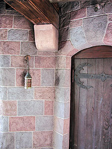 Entryway stamped vertical concrete overlay similar to a castle wood door and stone blocks in multiple stain concrete colors.