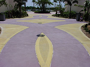 A purple and yellow concrete courtyard featuring a circular mag brush finish on the concrete.