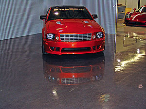 Red Ford Mustang in a auto show room whose floor is a slick shining concrete floor coating.