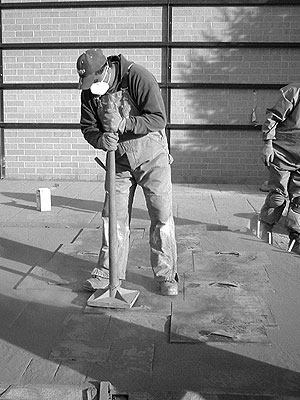 Concrete Stamping in cold weather tamping a stamp down with a long handled tamper while wearing appropriate safety gear.