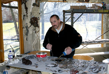 Vince Schrementi, seen here in his living room (under construction for the three years he and his family have lived in The Flintstone House) working on his mosaic, a wall of faces made out of bits of metal, glass and, of course, concrete.