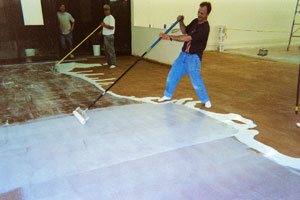 Applying Concrete Sealer with a plastic squeegee in a large room. The sealer looks white on the acid stained floor.