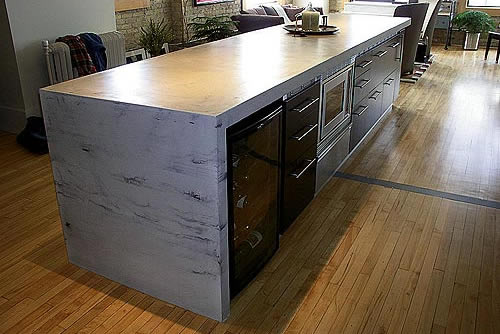 Kitchen Concrete Countertop from Specialized Construction Services with a waterfall edge. Looks like marble.
