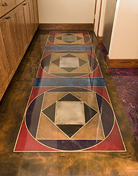 permanent area rug on a concrete floor stained in circles and triangles.