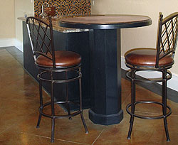 Concrete countertops sit atop a cylinder like base post over stained and engraved concrete floors.