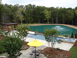 concrete patio and pool deck in North Carolina sits near an all concrete home.