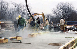Concrete construction crew working with freshly poured warm water concrete in a cold environment.