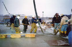 Large concrete crew wading in warm water concrete placing concrete with a concrete pump.
