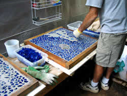 Placing blue glass pieces into the concrete one by one to create the mosaic look of the ocean