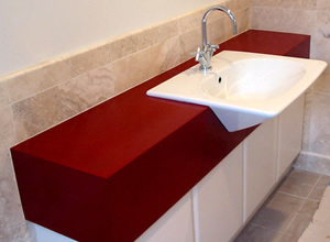 This red bathroom vanity combined a complicated shape with an unusual sink. The designer helped the installation team understand exactly how the sink should be mounted.
