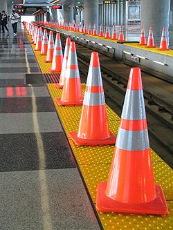 Safetly cones line the edge of a railway track.