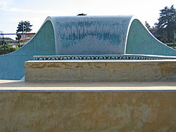 Skate park with a full pipe in the shape of a wave made from concrete.