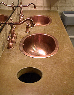 Concrete countertop in a brown and tan color is the perfect accent to the copper sink and faucet.