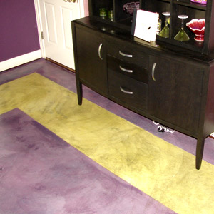 A green border on a purple concrete floor using stains.