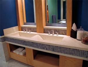 Concrete countertop with double sinks inlayed in a bathroom.