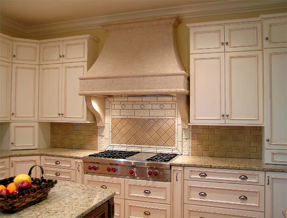Kitchen range hood that blends naturally into the kitchen of light colored granite.