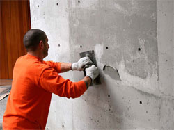 Steve Fox of Seattle's SAK and Patch applies a coat of Raeco's SkimWall in Seattle Gray. The project is a modern residential project whose architect wanted to retain the look of the cast-in-place concrete walls while masking the color variations between pour lines.