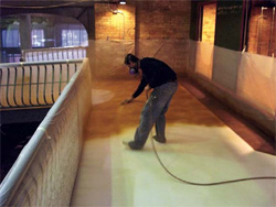 A contractor with a mask sprays the stain onto the concrete floor.