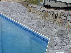 Stamped concrete pool deck that looks like natural stone.
