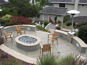 A perfect sitting area was created on the upper deck of this concrete patio with the firepit and wood chairs.