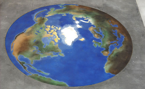 Stained concrete in the shape and colors of the world with blue ocean and browns and greens for topography.