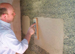 Lime Technology managing director Ian Pritchett applies samples of lime render on an interior wall of the chapel.