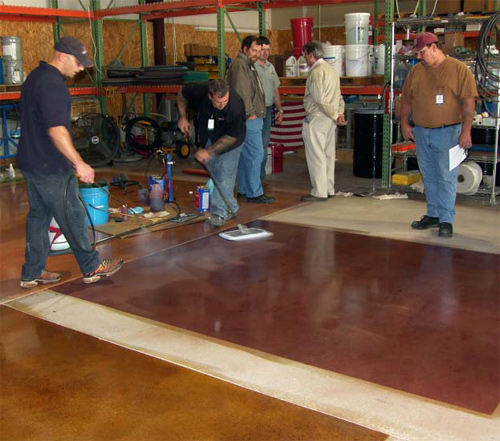 Jason Campbell (with sprayer) and Gary Vidal (with mop) of American Decorative Concrete Supply Co. show observers the correct way to apply ColorJuice to floors. They are spreading ADCSC's Proguard Stain Shield after a ColorJuice application. ADCSC conducts training at its facility every three months.