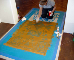 Applying the stain to the stencil before removing it.