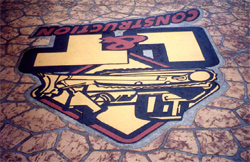 The finished L&T logo on the driveway, shown upside down, as seen from the house.