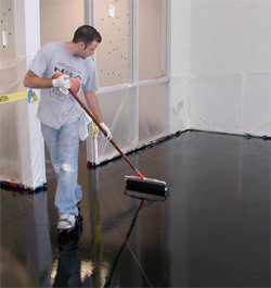 A man applying the coating to this floor using a broom technique.