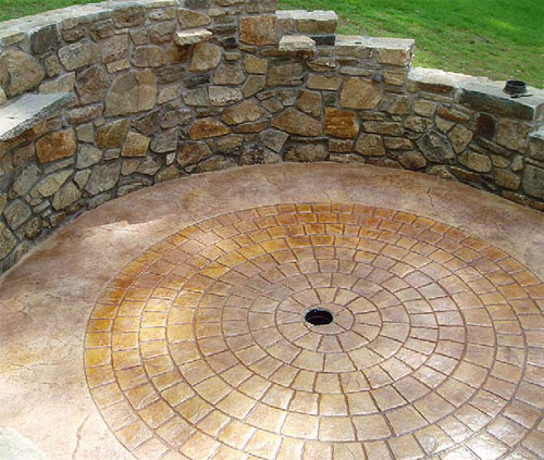 Stamped concrete circular brick pattern with a drain in the center.