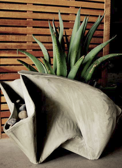 A gray concrete planter that has been formed with fabric.