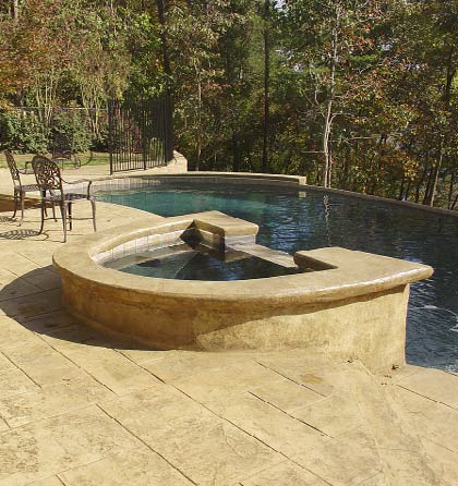 A serene pool deck that as been stamped and stained to blend in better to its natural setting.