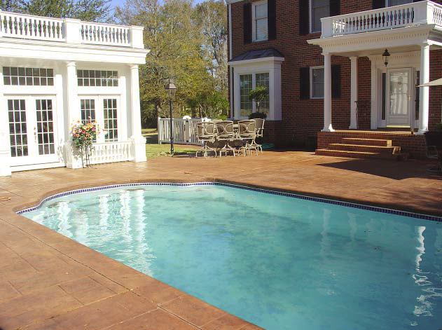 A crystal clear pool surrounded by a red pool deck that has imprinted concrete.