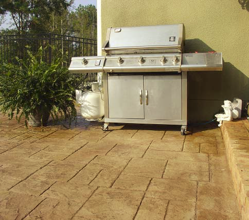 A grill sits on top of a stamped concrete patio.