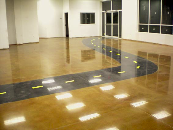 A concrete floor that has a faux road stained into it with yellow lines and a black road.