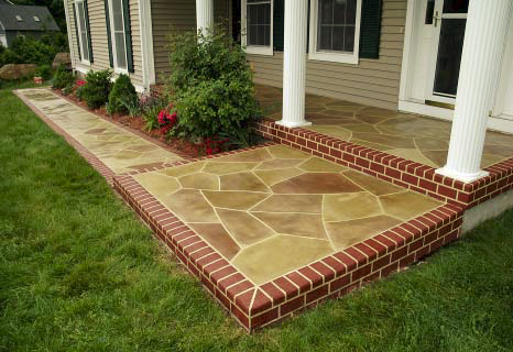 Custom Concrete Solutions LLC creates a concrete patio with faux brick like edges and natural looking stones stained in browns.