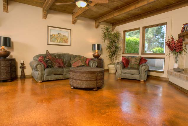 Amber stained concrete floors in busy family room with a round coffee table.