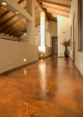 Long elegant hallway with high exposed beam ceilings with stained concrete floors.