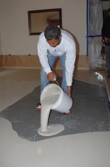 A conractor pours a self-leveler on a living-room floor.