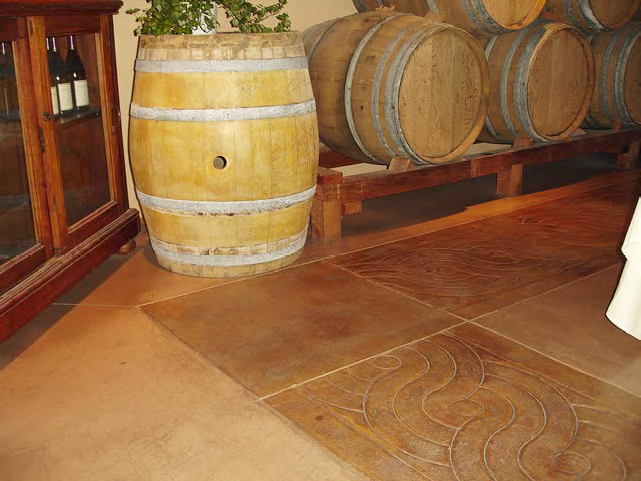 Concrete border in a darker color than the concrete floor butts up to wine barrels.