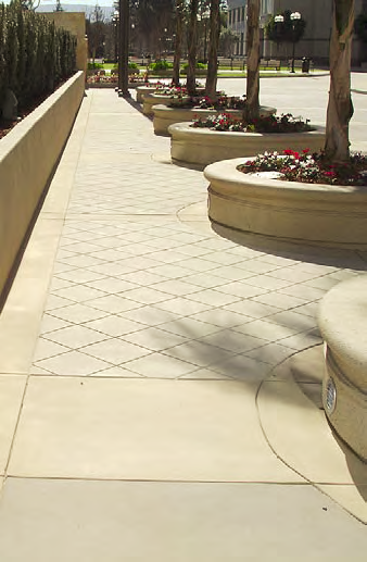 Concrete planters that are surrounded by stamped and integrally colored concrete.